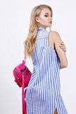 Beautiful blonde girl posing in studio on a white background in summer clothes Stock Photography