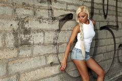 Beautiful blonde girl posing by the wall Stock Photography
