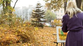 The young girl paints a picture in the autumn park. Beautiful blonde girl in the purple coat painting a picture on an easel in the autumn park, holding paints in stock photo