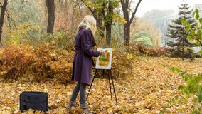 The young girl paints a picture in the autumn park. Beautiful blonde girl in the purple coat painting a picture on an easel in the autumn park, holding paints in royalty free stock photos