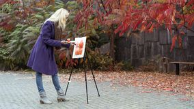 The young girl paints a picture in the autumn park. Beautiful blonde girl in the purple coat painting a picture on an easel, holding paints in hand. Colorful stock images