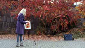 The young girl paints a picture in the autumn park. Beautiful blonde girl in the purple coat painting a picture on an easel, holding paints in hand. Colorful stock photography