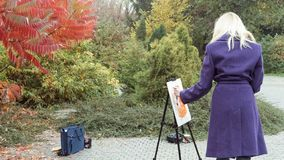 The young girl paints a picture in the autumn park. Beautiful blonde girl in the purple coat painting a picture on an easel, holding paints in hand. Colorful royalty free stock images