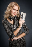 Beautiful blonde girl with purse. Beautiful blonde girl holding little black and white purse stock photography