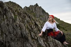 Beautiful blonde girl  with a red cloak on her head sitting on a rock. Beautiful blonde girl  with a red cloak on her head sitting on a rock Royalty Free Stock Photos
