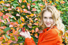 Beautiful blonde girl in the red coat. Beautiful young blonde girl in the red coat on a background of autumn color of leaves and berries Royalty Free Stock Photos