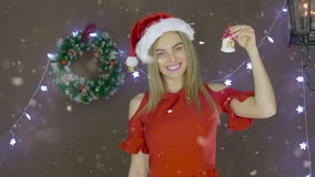 Beautiful blonde girl in red dress and Christmas hat ringing a bell on background of Christmas decorations stock video footage