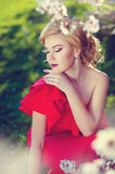 Beautiful blonde girl in a red dress costs about white flower royalty free stock images