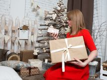 Beautiful blonde girl in red dress and New Year presents. New Year mood and interior. Choosing which gift to take, a bad look at a small box Royalty Free Stock Images