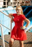 Beautiful blonde girl in red dress posing on stairs of big ship Royalty Free Stock Images