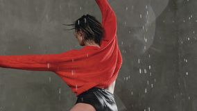 The beautiful blonde girl in red sweater dancing under the drops of rain in the studio against the background of a gray