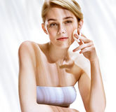 Beautiful blonde girl removing make up from her face. Stock Photo