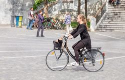 Beautiful blonde girl ride on bicycle on central square in Ljubljana, the capital of Slovenia. LJUBLJANA, SLOVENIA - SEPTEMBER 04 , 2018: Beautiful blonde girl stock photos