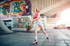 Beautiful blonde girl is riding in rollers in skate room. She is doing that very active. Girl wears pink top and shorts stock photo