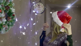 Beautiful blonde girl ringing a bell showing it`s almost Christmas on background of Christmas decorations stock video