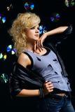 Beautiful blonde girl rocker. Potrait of beautiful blonde girl glam rocker in leather jacket. multiple shiny cds on dark background Stock Photos
