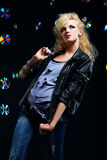 Beautiful blonde girl rocker. Potrait of beautiful blonde girl glam rocker in leather jacket. multiple shiny cds on dark background Stock Photos