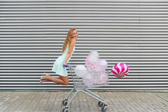 Beautiful blonde girl rolling shopping cart with color balloons. Royalty Free Stock Photography