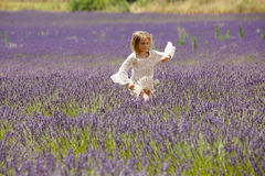 Beautiful blonde girl runs through a lavender field Royalty Free Stock Photos