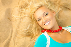 Beautiful blonde girl on sandy beach, portrait Royalty Free Stock Photo