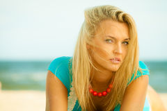 Beautiful blonde girl on sandy beach, portrait. Holidays, vacation travel and freedom concept. Beautiful blonde girl laying on sandy beach, portrait Stock Photo