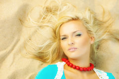 Beautiful blonde girl on sandy beach, portrait Royalty Free Stock Photography