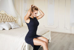 Beautiful blonde girl in a sexy black dress Royalty Free Stock Images