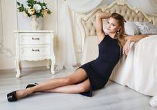 Beautiful blonde girl in a sexy black dress Stock Photo