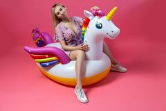A beautiful blonde girl in a sexy sundress with slim legs in white sneakers sits on an inflatable multi-colored unicorn royalty free stock images