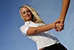 Beautiful blonde girl shakes hand Royalty Free Stock Photos