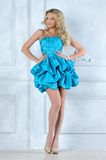 Beautiful blonde girl in short blue dress. Beautiful blonde girl in short blue evening dress Royalty Free Stock Photos
