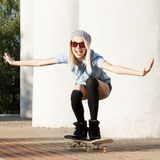 Beautiful blonde girl in short shorts with skateboard. Beautiful smiling blond girl in sunglasses, shorts and stockings rides happily on skateboard Royalty Free Stock Images