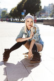 Beautiful blonde girl in short shorts with skateboard. Blond girl in short shorts, jeans coat, black stockings and grey hat sits on skateboard and bites Royalty Free Stock Photography