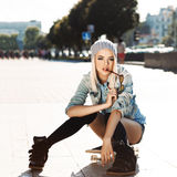 Beautiful blonde girl in short shorts with skateboard. Blond girl in short shorts, jeans coat, black stockings and grey hat sits on skateboard and bites Stock Photo