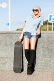 Beautiful blonde girl in short shorts with skateboard. Smiling blond girl in short shorts, checked sleeveless shirt, black stockings and sunglasses leans on Royalty Free Stock Photo