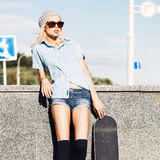 Beautiful blonde girl in short shorts with skateboard. Smiling blond girl in short shorts, checked sleeveless shirt, black stockings and sunglasses leans on Royalty Free Stock Photos