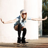 Beautiful blonde girl in short shorts with skateboard. Beautiful smiling blond girl in sunglasses, shorts and stockings rides happily on skateboard Royalty Free Stock Photos