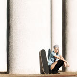 Beautiful blonde girl in short shorts with skateboard. Beautiful girl in short shorts and stockings with skateboard sits on her haunches near  columns on sunny Royalty Free Stock Photography