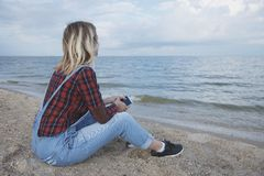Beautiful blonde girl sits on the beach and looks at the sea stock photo
