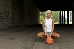 Beautiful blonde girl is sitting with basketball Royalty Free Stock Photography