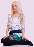 Beautiful blonde girl sitting on chair Stock Images
