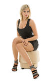 Beautiful blonde girl is sitting on an ottoman Stock Photos