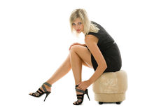 Beautiful blonde girl is sitting on an ottoman Royalty Free Stock Images