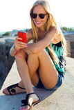 Beautiful blonde girl sitting on the roof with mobile phone. stock photography