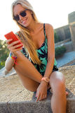 Beautiful blonde girl sitting on the roof with mobile phone. Stock Photos