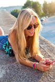 Beautiful blonde girl sitting on the roof with mobile phone. Royalty Free Stock Image
