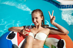 Beautiful blonde girl smiling, drinking cocktail, swimming in pool. Stock Photos