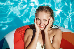 Beautiful blonde girl smiling, resting, relaxing, swimming in pool. Copy space stock image