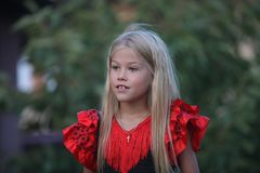 Beautiful blonde girl in a Spanish dress. Beautiful blonde girl in in a Spanish dress in the garden Stock Photo