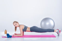 Beautiful blonde girl in sportswear does exercises on fitness Mat on gray background stock photo